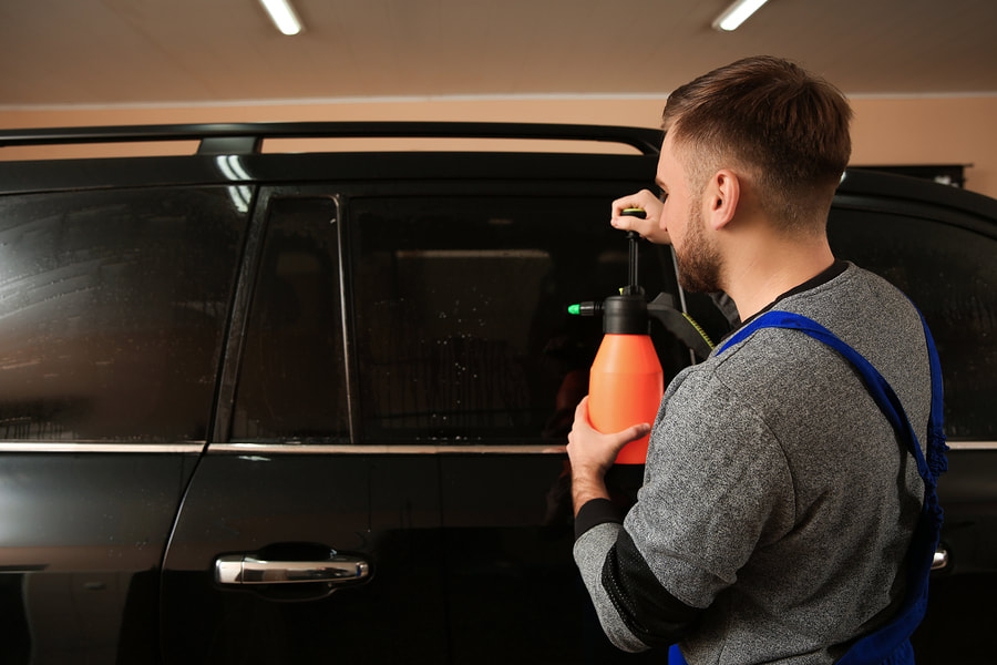 man installling a tint in the car