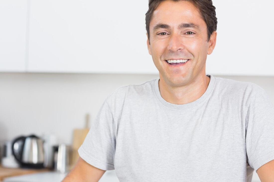 man smiling in a white shirt